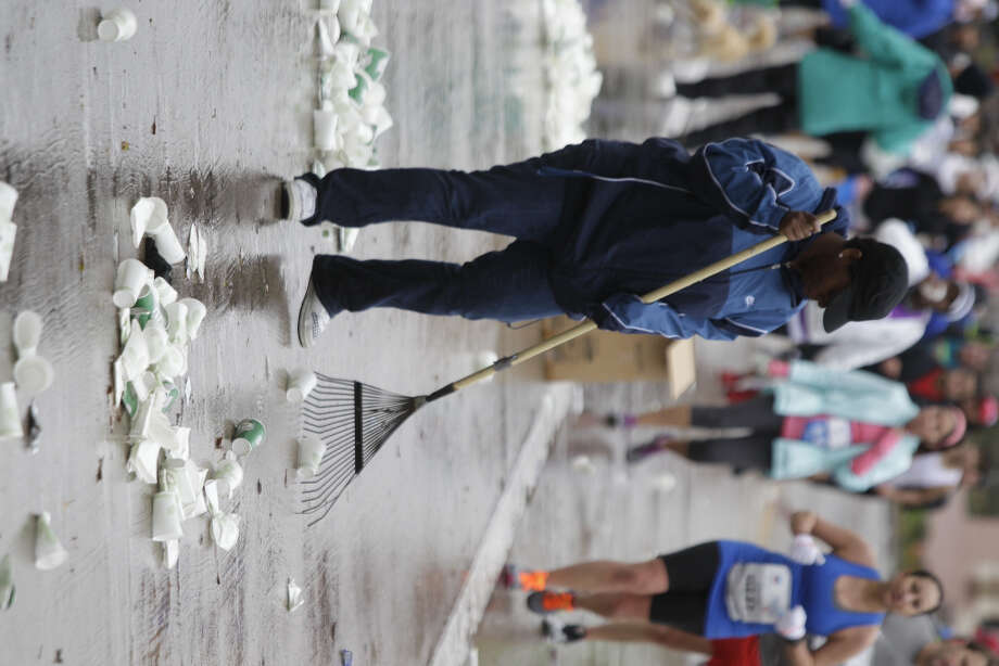 Volunteer Ashton McKinley rakes empty cups dropped by runners along University near mile 13 of the Chevron Houston Marathon.
