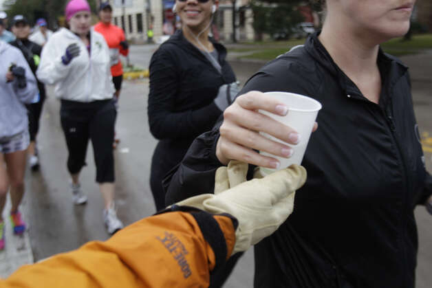 Volunteer Ronny Cuenod hands out water to runners along University near mile 13 of the Chevron Houston Marathon.