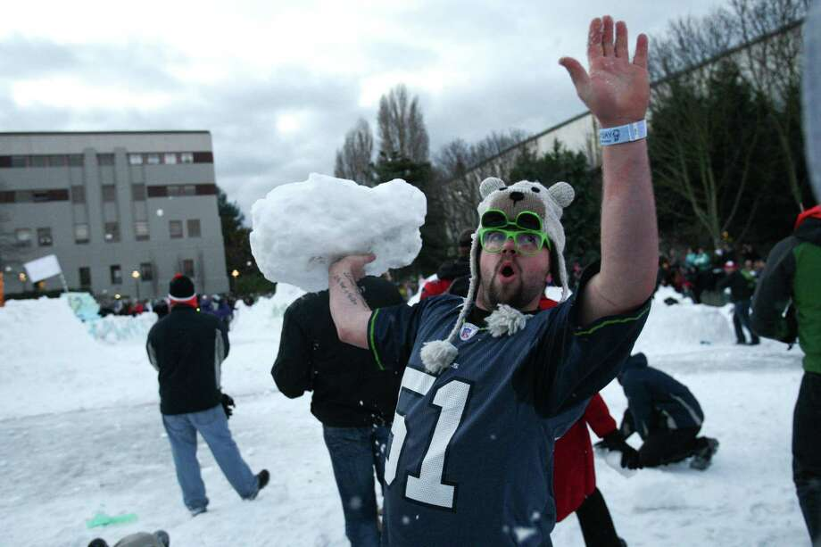 "A man hoists an ice chunk during ""Snow Day."" Photo: JOSHUA TRUJILLO, SEATTLEPI.COM / SEATTLEPI.COM"