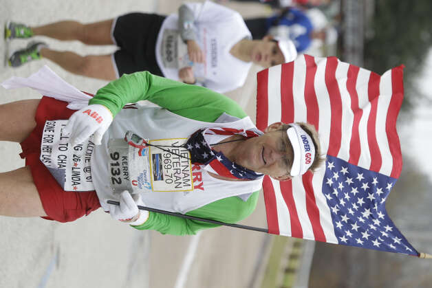 Kerry Walsh carries a U.S. flag as he runs along Allen Parkway near mile 24 of the Chevron Houston Marathon.