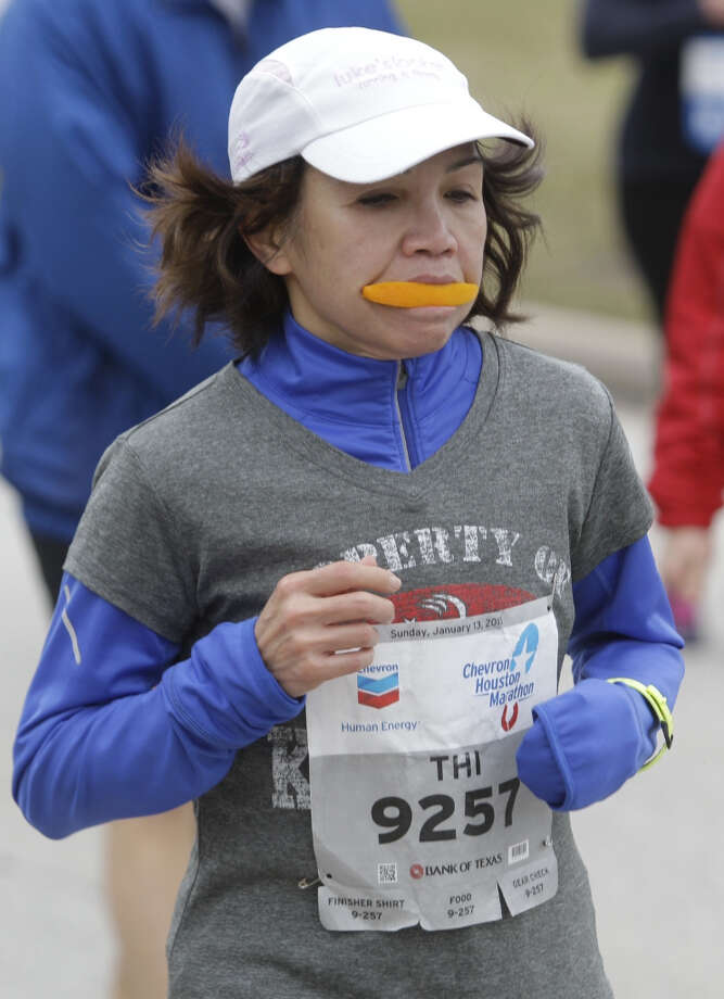 Thi Nguyen runs along Allen Parkway near mile 24 of the Chevron Houston Marathon.