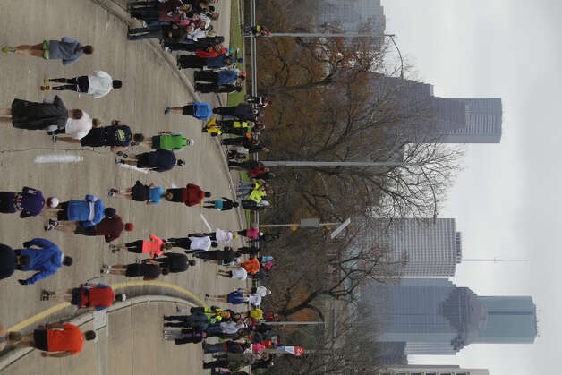Runners pass along Allen Parkway near mile 24 of the Chevron Houston Marathon.