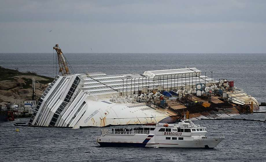 A small boat carries relatives and survivors past the Costa Concordia. The ship rammed a reef and sank on Jan. 13, 2012, off the Italian island of Giglio. Photo: Filippo Monteforte, AFP/Getty Images