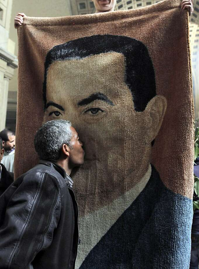 A loyalist kisses the image of Hosni Mubarak, who appealed his life sentence in the killing of protesters. Photo: Amr Nabil, Associated Press