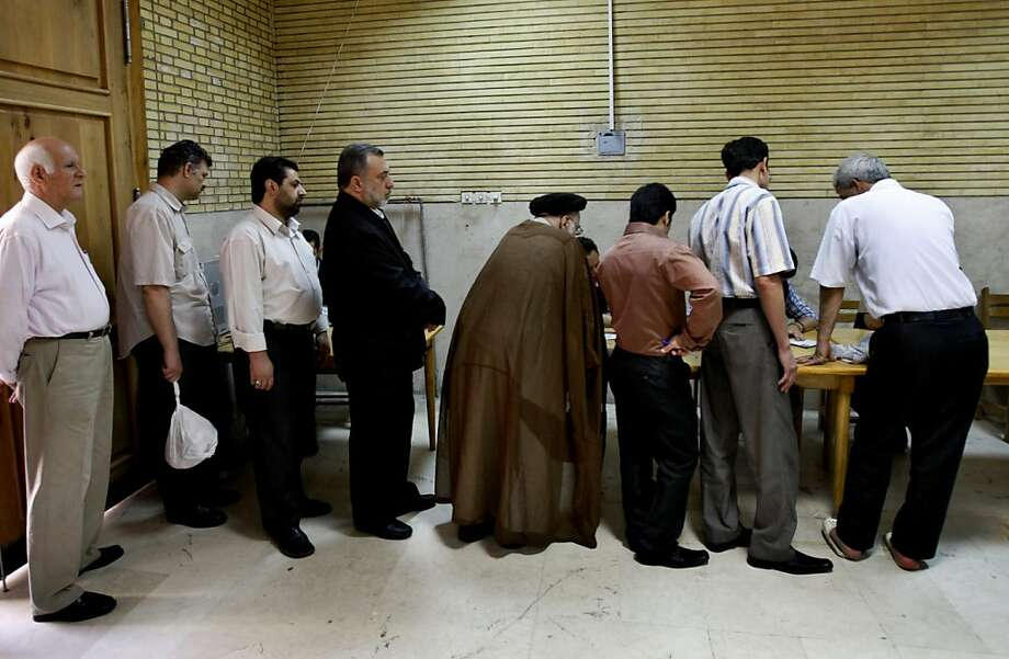 In this Friday, June 12, 2009 photo, Iranian men line up to get ballots for the presidential elections at a polling station, in Tehran, Iran. Elections to pick Iran's next president are still five months away, but that's not too early for some warning shots by the country's leadership. The message to anyone questioning the openness of the June vote: Keep quiet. (AP Photo/Vahid Salemi) Photo: Vahid Salemi, Associated Press