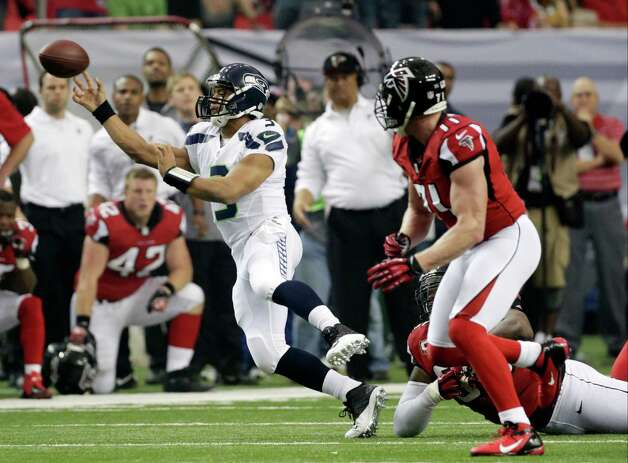 Seattle Seahawks quarterback Russell Wilson (3) makes the throw under pressure during the first half of an NFC divisional playoff NFL football game against the Seattle Seahawks Sunday, Jan. 13, 2013, in Atlanta. (AP Photo/Dave Martin) Photo: Dave Martin, Associated Press / AP