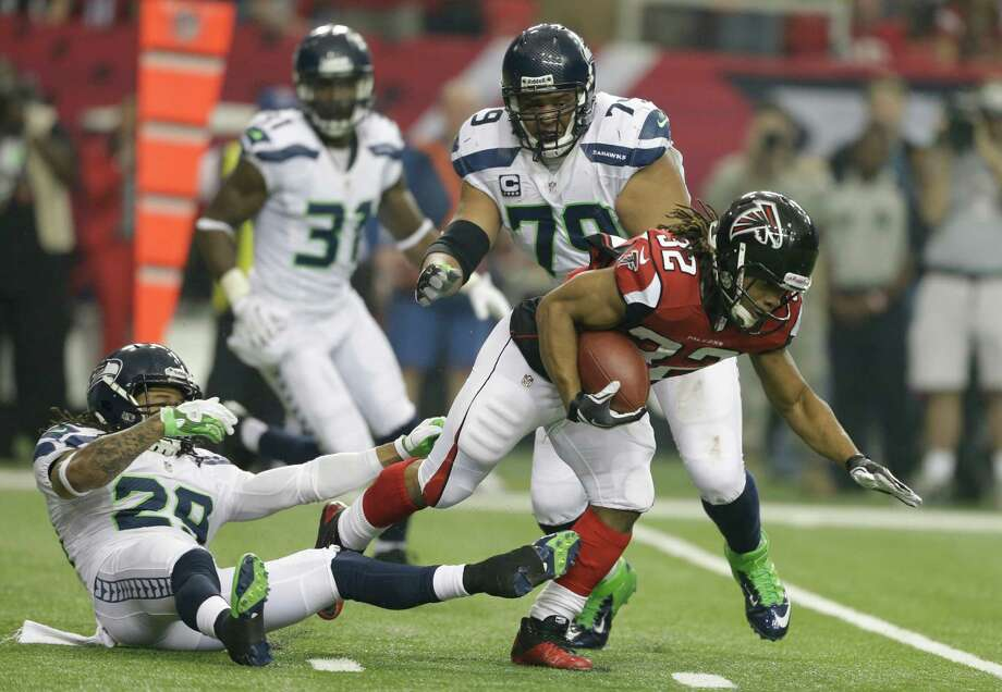 Atlanta Falcons running back Jacquizz Rodgers (32) breaks the tackle of Seattle Seahawks free safety Earl Thomas (29) and defensive end Red Bryant (79) during the first half of an NFC divisional playoff NFL football game Sunday, Jan. 13, 2013, in Atlanta. (AP Photo/David Goldman) Photo: David Goldman, Associated Press / AP