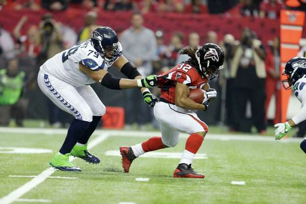 Seattle Seahawks' Red Bryant tries to stop Atlanta Falcons' Jacquizz Rodgers (32) during the first half of an NFC divisional playoff NFL football game Sunday, Jan. 13, 2013, in Atlanta. (AP Photo/David Goldman) Photo: David Goldman, Associated Press / AP