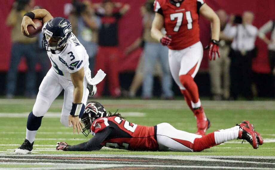 Seattle Seahawks' Russell Wilson runs during the first half of an NFC divisional playoff NFL football game against the Atlanta Falcons Sunday, Jan. 13, 2013, in Atlanta. (AP Photo/Dave Martin) Photo: Dave Martin, Associated Press / AP