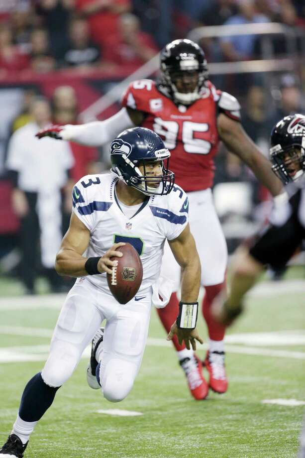 Seattle Seahawks' Russell Wilson scrambles during the first half of an NFC divisional playoff NFL football game against the Atlanta Falcons Sunday, Jan. 13, 2013, in Atlanta. (AP Photo/Dave Martin) Photo: Dave Martin, Associated Press / AP