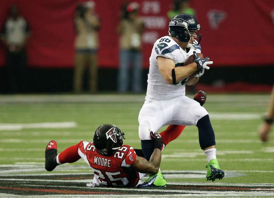 Seattle Seahawks' Zach Miller catches a pass with Atlanta Falcons' William Moore defending during the first half of an NFC divisional playoff NFL football game Sunday, Jan. 13, 2013, in Atlanta. (AP Photo/John Bazemore) Photo: John Bazemore, Associated Press / AP