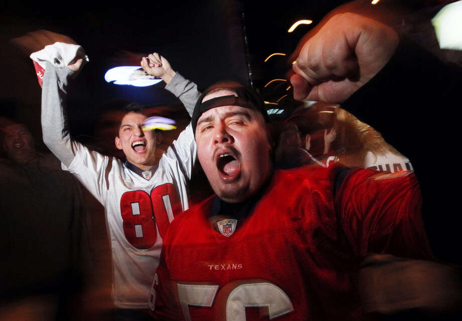 Carlo Medellin, right, and Cody Vela, celebrate a Texans defensive stop on third down at SRO Sports Bar and Cafe.