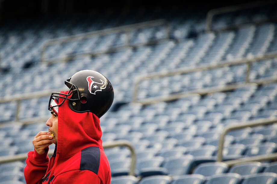A Texans fan munches on popcorn as he watches the teams warm up. Photo: Smiley N. Pool, Houston Chronicle / © 2013  Houston Chronicle