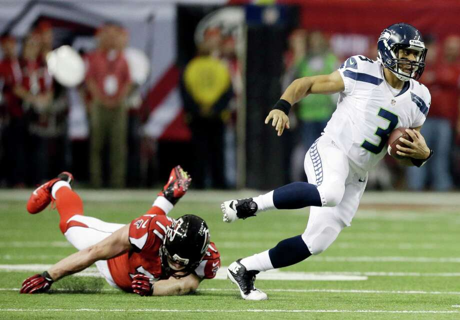Seattle Seahawks quarterback Russell Wilson (3) runs past Atlanta Falcons defensive end Kroy Biermann (71) during the first half of an NFC divisional playoff NFL football game Sunday, Jan. 13, 2013, in Atlanta. (AP Photo/David Goldman) Photo: David Goldman, Associated Press / AP
