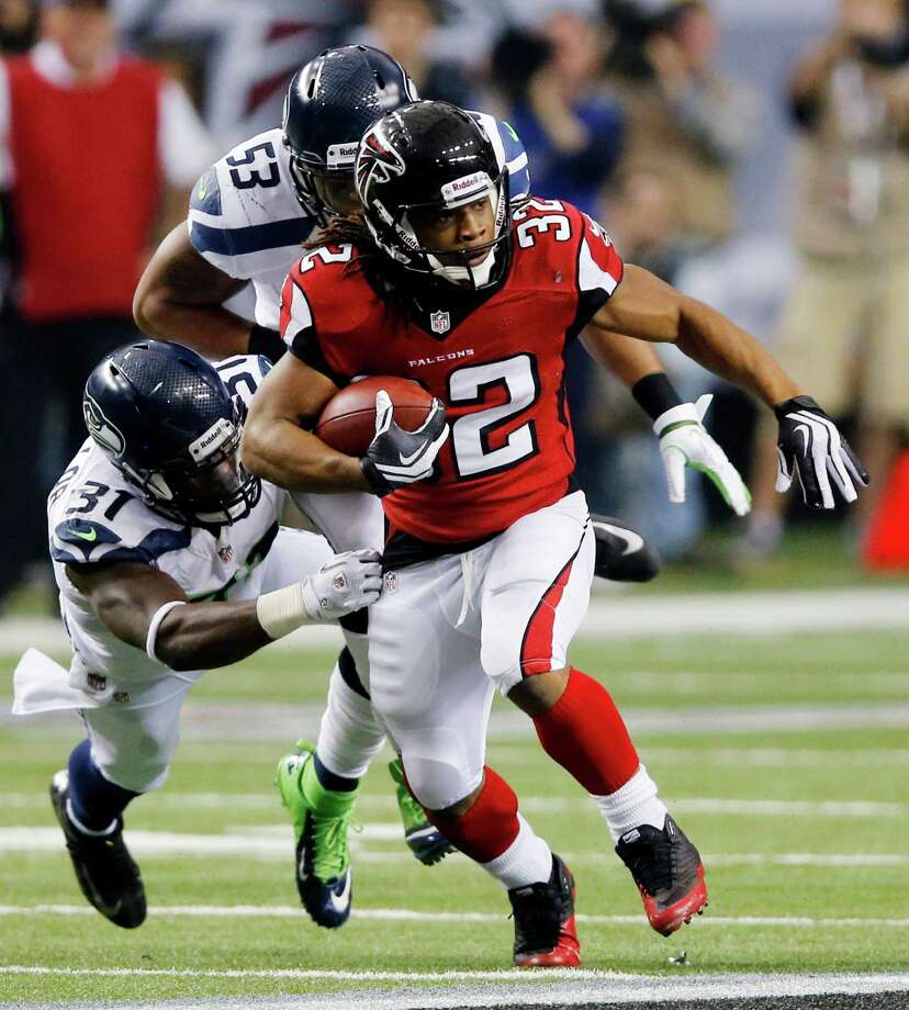 Atlanta Falcons running back Jacquizz Rodgers (32) works against Seattle Seahawks outside linebacker Malcolm Smith (53) and strong safety Kam Chancellor (31) during the second half of an NFC divisional playoff NFL football game Sunday, Jan. 13, 2013, in Atlanta. (AP Photo/John Bazemore) Photo: John Bazemore, Associated Press / AP