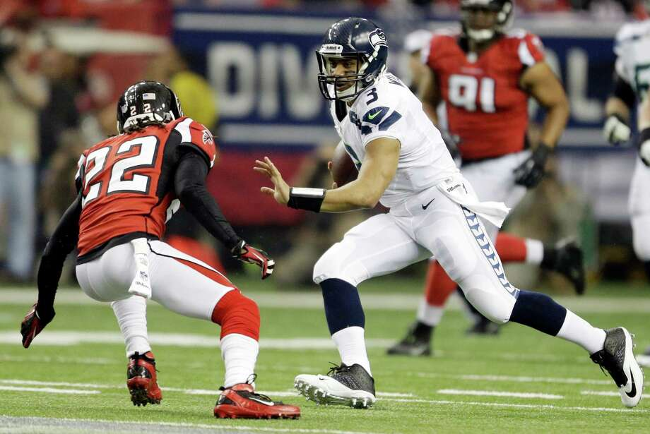 Seattle Seahawks quarterback Russell Wilson (3) tries to run past Atlanta Falcons' Asante Samuel (22) during the first half of an NFC divisional playoff NFL football game Sunday, Jan. 13, 2013, in Atlanta. (AP Photo/David Goldman) Photo: David Goldman, Associated Press / AP