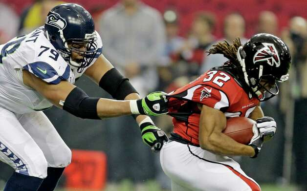 Seattle Seahawks' Red Bryant (79) tries to stop Atlanta Falcons' Jacquizz Rodgers (32) during the first half of an NFC divisional playoff NFL football game Sunday, Jan. 13, 2013, in Atlanta. (AP Photo/David Goldman) Photo: David Goldman, Associated Press / AP