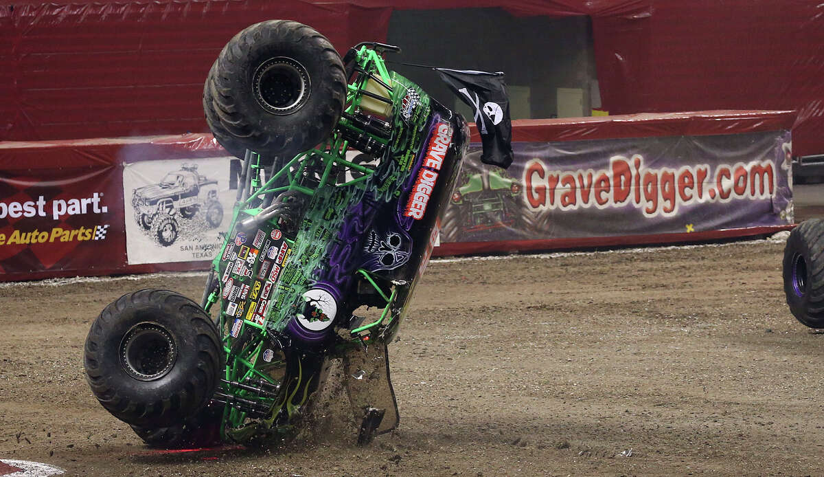 Grave Digger takes a spill during a second round race against Mohawk Warrior at the Advance Auto Parts Monster Jam in the Alamodome, Sunday, Jan. 13, 2013.