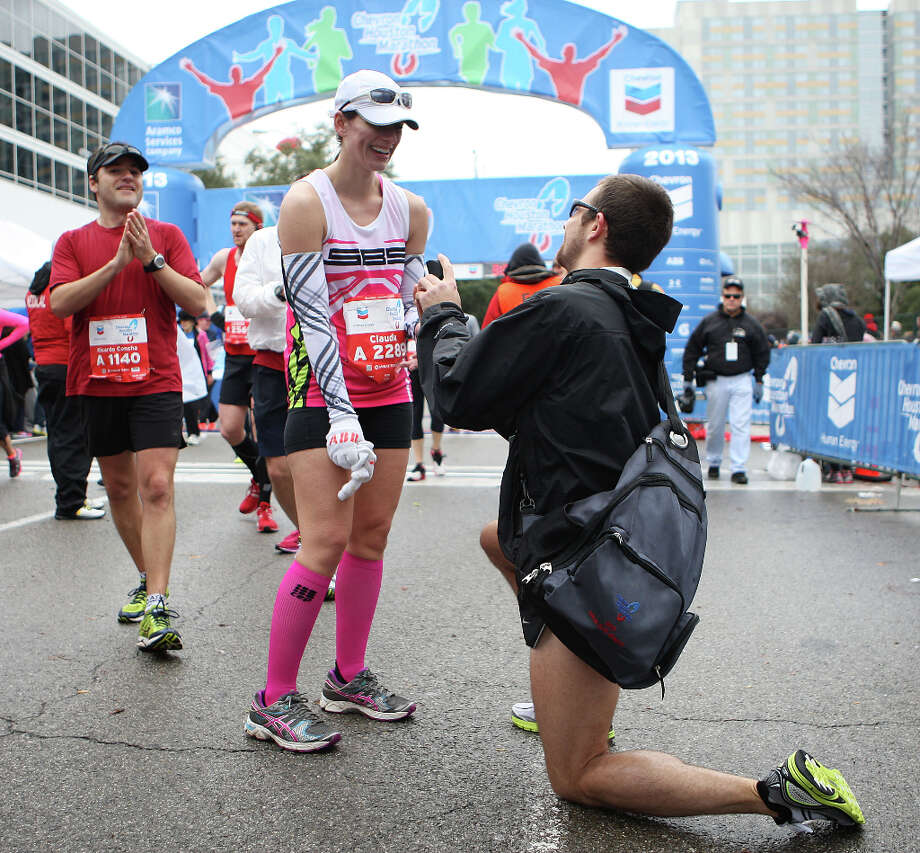 Ryan Smith right, proposes marriage to his girlfriend Claudia Behring after running the Chevron Houston Marathon. Photo: James Nielsen, Chronicle / © Houston Chronicle 2013