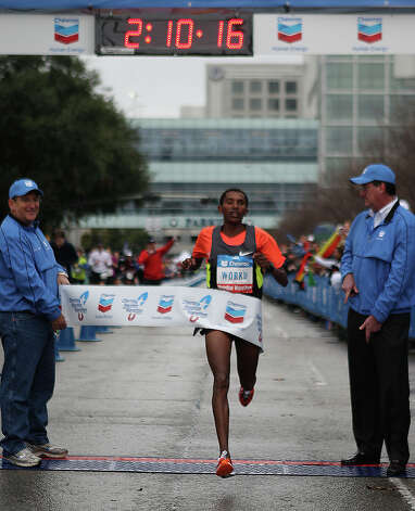 Bazu Worku crosses the finish line to win the Chevron Houston Marathon. Photo: James Nielsen, Chronicle / © Houston Chronicle 2013