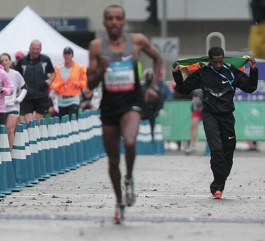 Bazu Worku right dances on the course after winning the men's division of the Chevron Houston Marathon. Photo: James Nielsen, Chronicle / © Houston Chronicle 2013