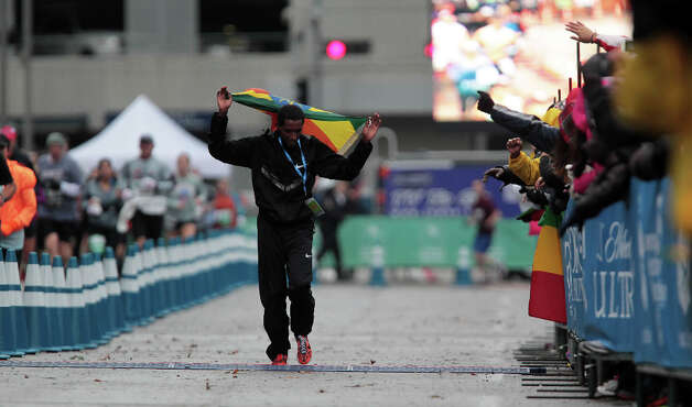 Bazu Worku walks along the course while draped by an Ethiopian flag after winning the men's division. Photo: James Nielsen, Chronicle / © Houston Chronicle 2013
