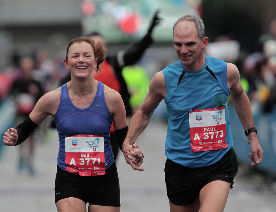 Gail Illich left, runs hand-in-hand with Paul Illich as the pair nears the finish line. Photo: James Nielsen, Chronicle / © Houston Chronicle 2013