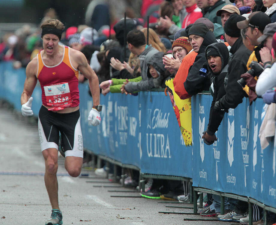 Clay Emge is cheered on by spectators as he nears the finish line. Photo: James Nielsen, Chronicle / © Houston Chronicle 2013