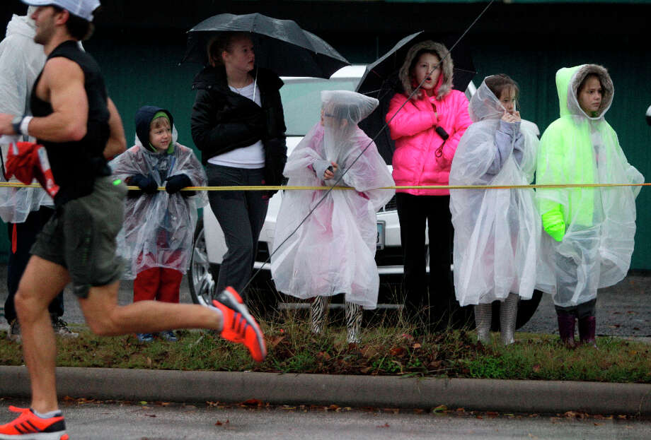 Spectators watch runners in the rain along Studewood near White Oak during the Chevron Houston Marathon and Aramco Houston Half Marathon. Photo: Melissa Phillip, Houston Chronicle / © 2013 Houston Chronicle