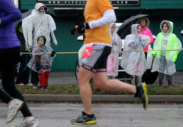 Spectators watch runners in the rain along Studewood near White Oak during the Chevron Houston Marathon and Aramco Houston Half Marathon. Photo: Melissa Phillip, Houston Chronicle / © 2013 Houston Chronicle
