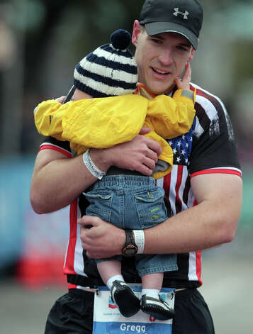 Gregg Frashure carries his son Houston Frashure across the finish line. Photo: James Nielsen, Chronicle / © Houston Chronicle 2013
