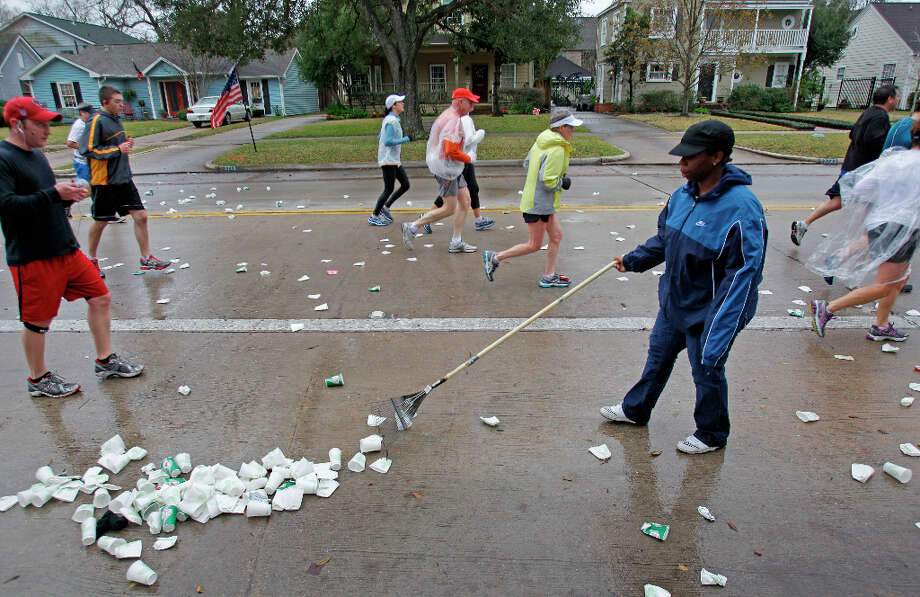 Volunteer Ashton McKinley rakes cups and other trash dropped by runners along University near mile 13 of the Chevron Houston Marathon. Photo: Melissa Phillip, Houston Chronicle / © 2013 Houston Chronicle