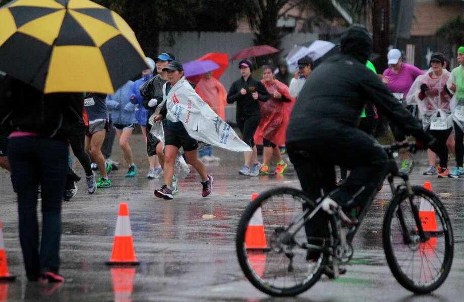 Runners move along Studewood near White Oak during the Chevron Houston Marathon and Aramco Houston Half Marathon. Photo: Melissa Phillip, Houston Chronicle / © 2013 Houston Chronicle