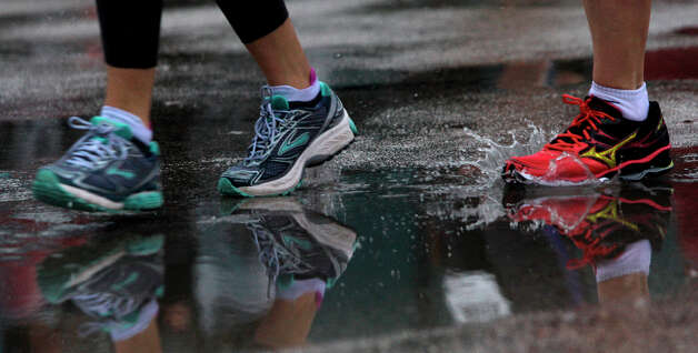 Runners move through the puddles along Studewood near White Oak during the Chevron Houston Marathon and Aramco Houston Half Marathon. Photo: Melissa Phillip, Houston Chronicle / © 2013 Houston Chronicle