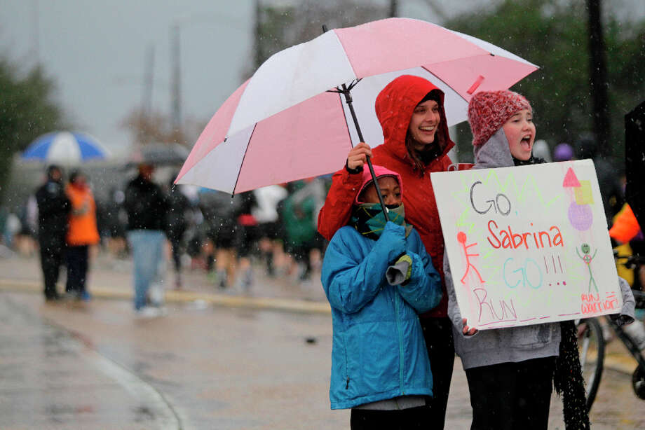 Lydia Jackson, 12, left, Stephanie Hruzek, center, and Samantha Green, 11, right, wait in the rain for Samantha's sister, Sabrina Green, to run past them along Studewood near White Oak during the Chevron Houston Marathon and Aramco Houston Half Marathon. Photo: Melissa Phillip, Houston Chronicle / © 2013 Houston Chronicle