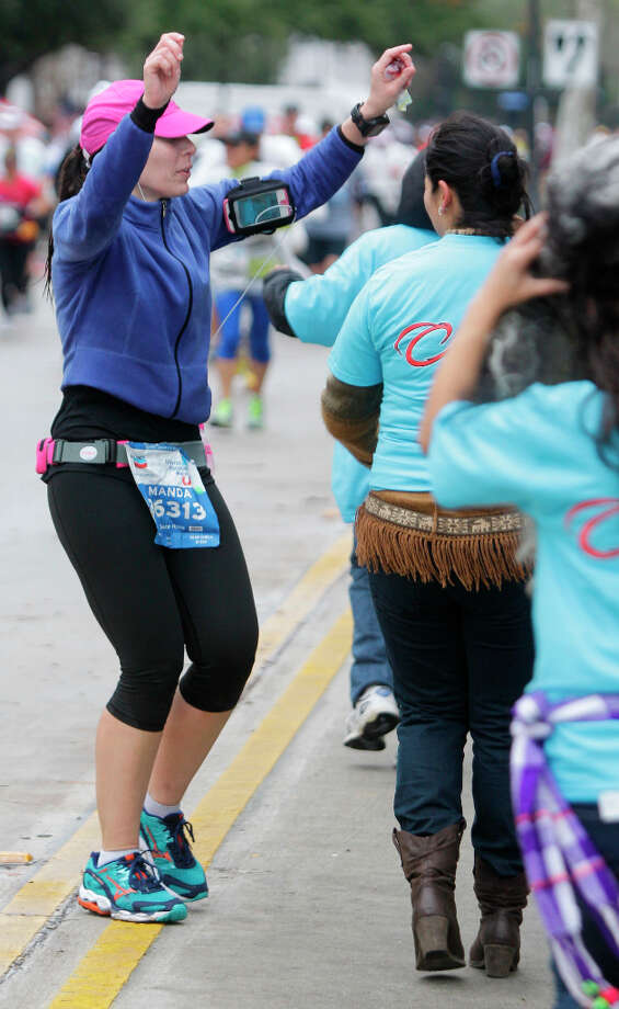 Runner Amanda McClure dances with Bolivian dance group along University near mile 13 of the Chevron Houston Marathon. Photo: Melissa Phillip, Houston Chronicle / © 2013 Houston Chronicle