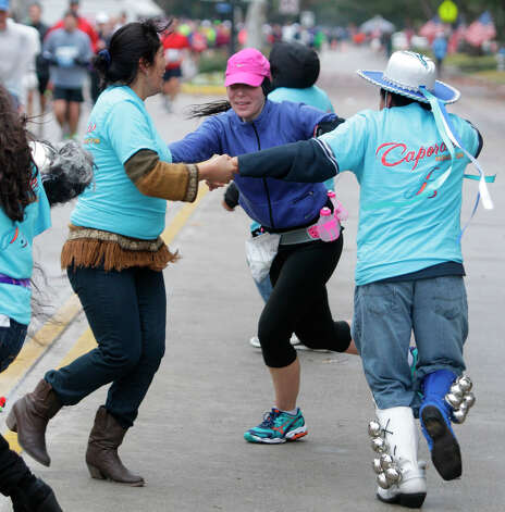 Bolivian dancers Janeth Flores, left, and Henry Patino, right, dance with runner Amanda McClure, center, along University near mile 13 of the Chevron Houston Marathon. Photo: Melissa Phillip, Houston Chronicle / © 2013 Houston Chronicle