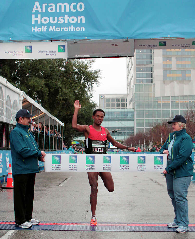 Feyisa Lilesa, of Ethiopia, crosses the finish line to win the men's division of the Half Marathon. Photo: James Nielsen, Associated Press / Houston Chronicle