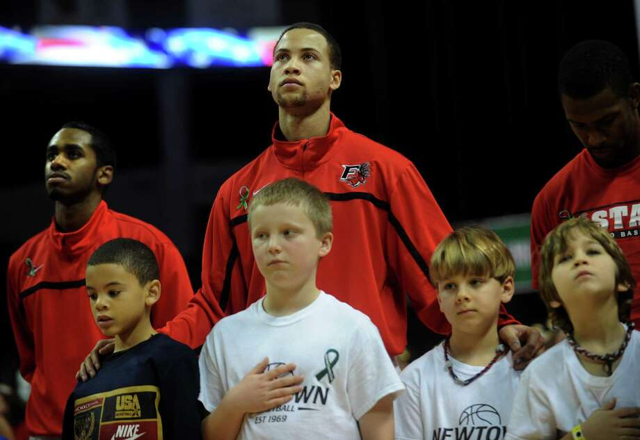 From left; Fairfield basketball players Steve Johnston, Colin Nickerson, and Derek Needham stand on the court with Newtown students during the playing of the National Anthem before Sunday's game versus Niagara at the Webster Bank Arena in Bridgeport on Sunday, January 13, 2013. Photo: Brian A. Pounds