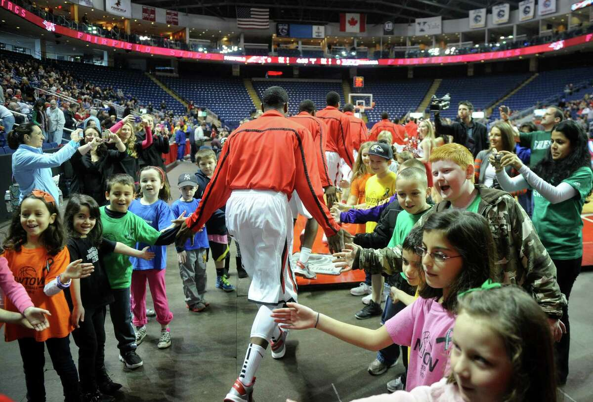 Newtown students form a high five tunnel welcoming Fairfield players to the court before the start of the Stags' men's basketball matchup with Niagara at the Webster Bank Arena in Bridgeport on Sunday, January 13, 2013.