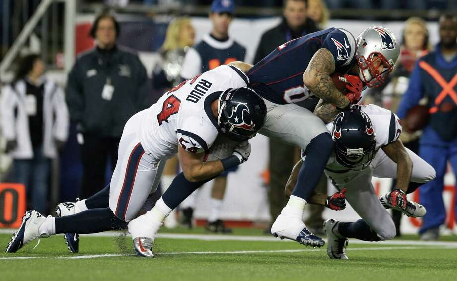 New England Patriots tight end Aaron Hernandez is tackled by Houston Texans linebacker Barrett Ruud (54) and Johnathan Joseph, right, during the first half of an AFC divisional playoff NFL football game in Foxborough, Mass., Sunday, Jan. 13, 2013. (AP Photo/Elise Amendola) Photo: Elise Amendola, Associated Press / AP