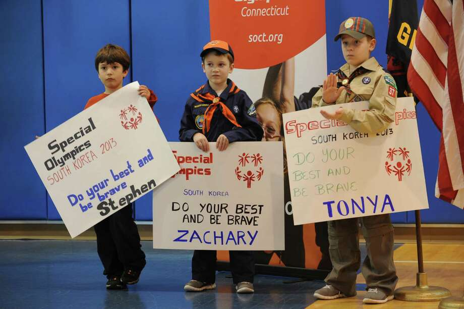 Boy Scouts Mark Casa, 7, Doyle Zisson, 7, and Will Zisson, 10, hold posters for the special Olympics, in Greenwich, in Conn. Sunday, Jan. 13, 2013, at a send-off party for Special Olympics athletes who will be going to South Korea compete in the Special Olympics World Winter Games in the home of Alex and Kristin Zisson. Photo: Helen Neafsey / Greenwich Time
