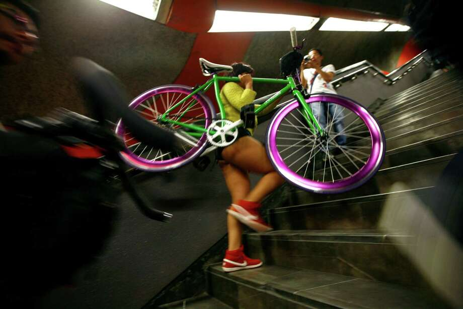 "Carrying a bike, a participant in the annual ""No Pants Subway Ride"" transfers to another train in Mexico City, Sunday. Photo: AP"