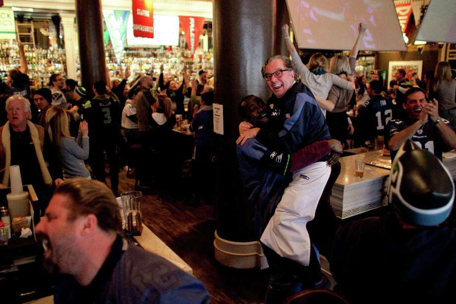 A fan hoists FX McRory's sports bar owner Mick McHugh as the Seahawks score a late touchdown against the Atlanta Falcons during an NFL playoff game in Atlanta on Sunday, January 13, 2013. The Hawks fell to the Falcons, ending their season. Photo: JOSHUA TRUJILLO, SEATTLEPI.COM / SEATTLEPI.COM