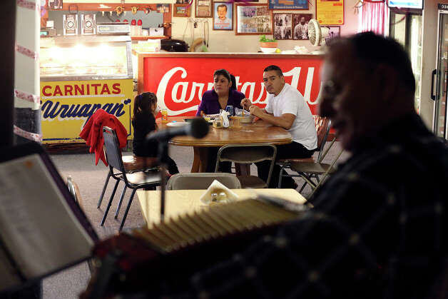 The Lares family (from left), Lupita, Maria and Armando, eat their breakfast as Santiago Jimenez Jr., a legendary conjunto accordionist and National Endowment for the Arts Heritage Fellowship recipient, plays at Carnitas Uruapan. Photo: Jerry Lara, San Antonio Express-News / © 2013 San Antonio Express-News