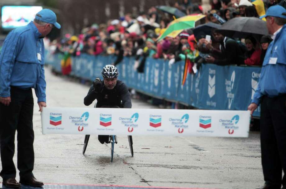 Grant Berthiaume of Tucson, Ariz., crosses the finish line in 2 hours, 12 minutes, 29 seconds to win the wheelchair division of the Chevron Houston Marathon on Sunday. Photo: James Nielsen, Staff / © Houston Chronicle 2013