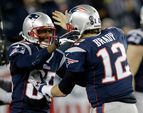 New England Patriots quarterback Tom Brady, right, congratulates teammate Brandon Lloyd after Loyd's five-yard touchdown pass from Brady during the second half of an AFC divisional playoff NFL football game against the Houston Texans in Foxborough, Mass., Sunday, Jan. 13, 2013. (AP Photo/Elise Amendola) Photo: Elise Amendola, Associated Press / AP