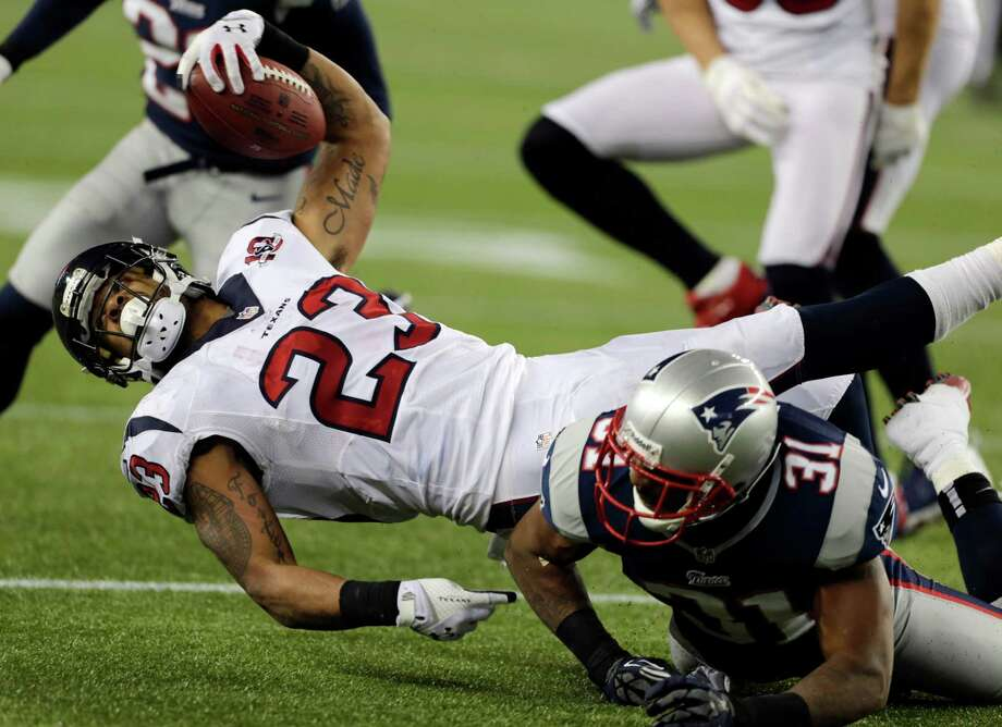 Houston Texans running back Arian Foster reaches forward for a first down after being tackled by New England Patriots cornerback Aqib Talib (31)during the second half of an AFC divisional playoff NFL football game in Foxborough, Mass., Sunday, Jan. 13, 2013. (AP Photo/Charles Krupa) Photo: Charles Krupa, Associated Press / AP