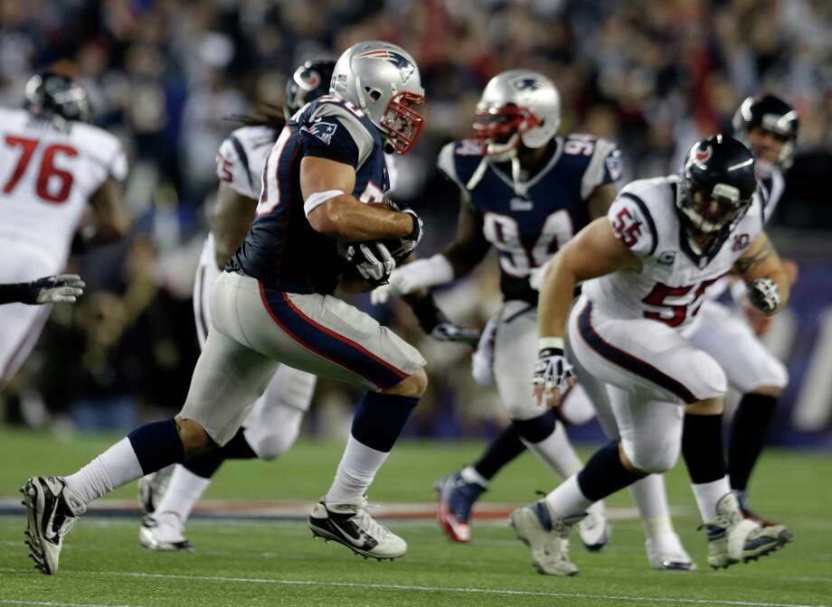 New England Patriots defensive end Rob Ninkovich (50) runs with the ball after intercepting a pass intended for Houston Texans fullback James Casey as he is chased by Texans center Chris Myers (55)during the second half of an AFC divisional playoff NFL football game in Foxborough, Mass., Sunday, Jan. 13, 2013. (AP Photo/Elise Amendola) Photo: Elise Amendola, Associated Press / AP