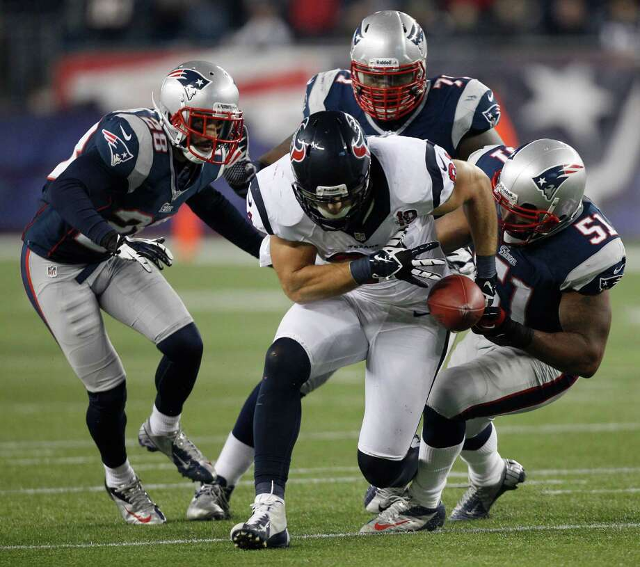 Houston Texans tight end Owen Daniels loses the ball while being stopped by New England Patriots' Steve Gregory, Brandon Deaderick and Jerod Mayo during the second half of an AFC divisional playoff NFL football game in Foxborough, Mass., Sunday, Jan. 13, 2013. The play had been stopped before Daniels dropped the ball. (AP Photo/Stephan Savoia) Photo: Stephan Savoia, Associated Press / AP
